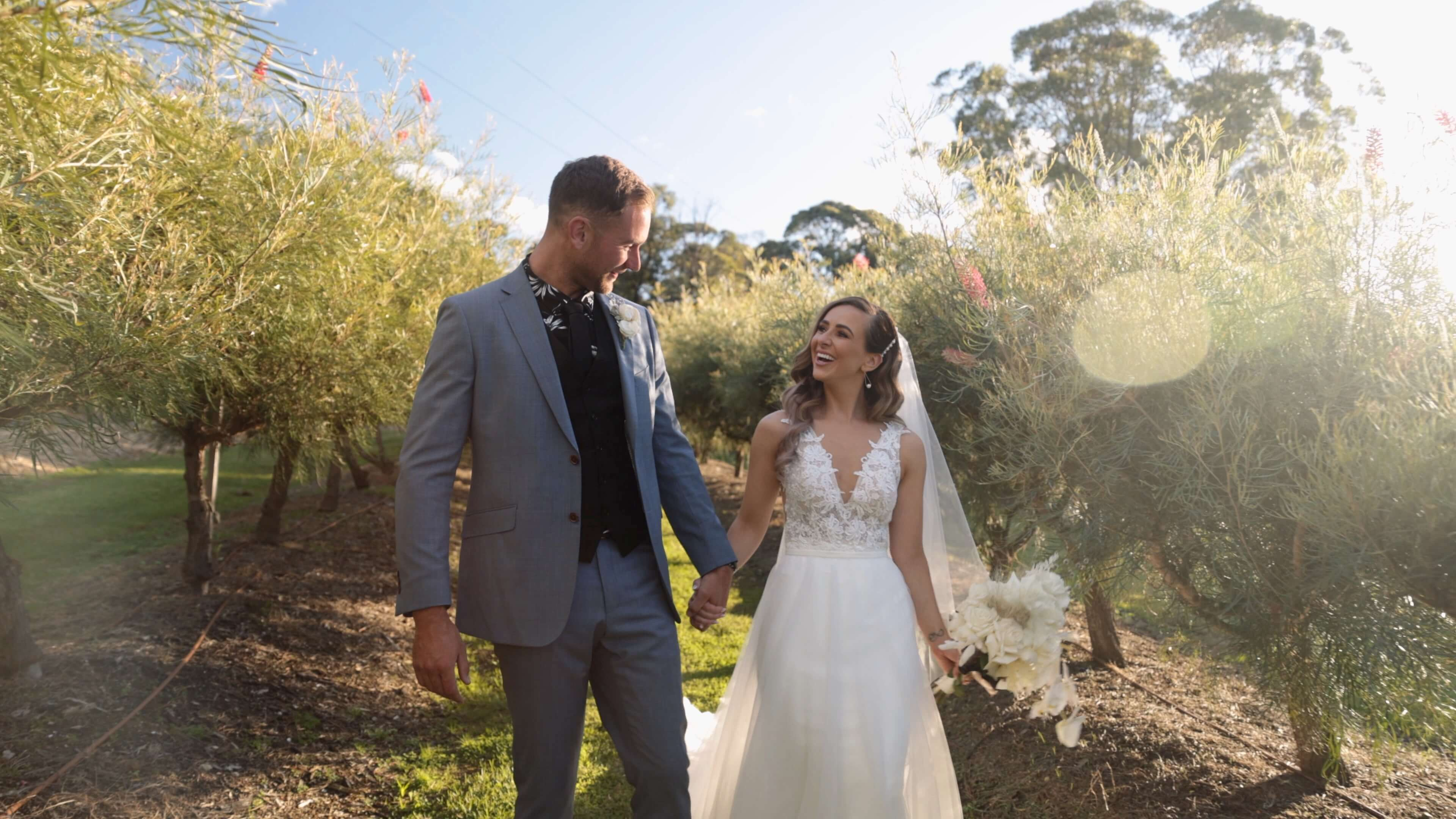 Newly married walking in a sunny orchard - wedding videography services in the Southern Highlands, Kangaroo Valley, Wollongong, and surrounding areas - Lovereel